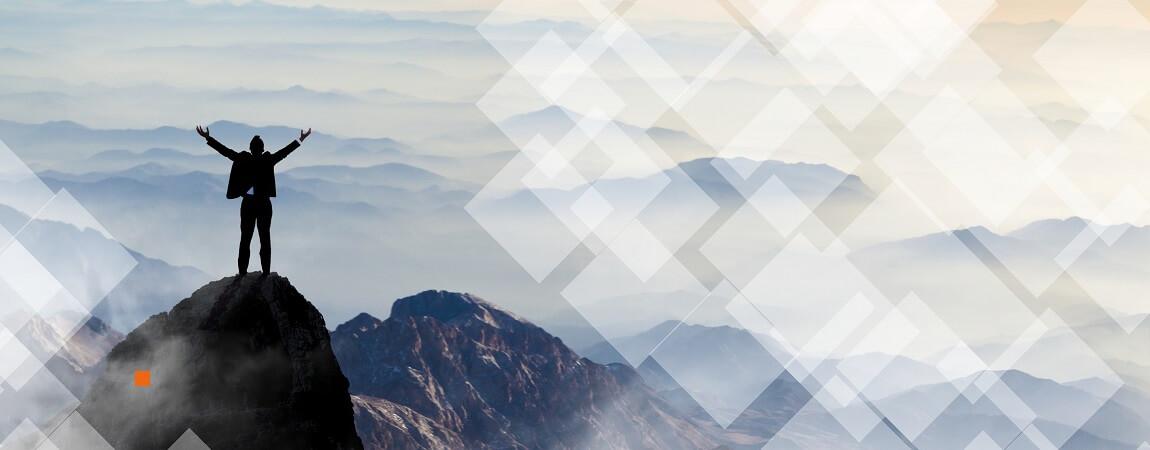 Mann steht auf einem Berggipfel und hat die höchste Position erreicht