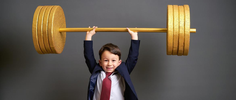Junge im Anzug stemmt Gewichte