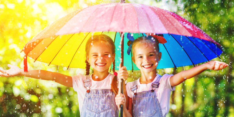 Zwei Mädchen mit Regenbogen-Regenschirm im Regen - die Zwillinge stehen für Google Ads und Bing Ads