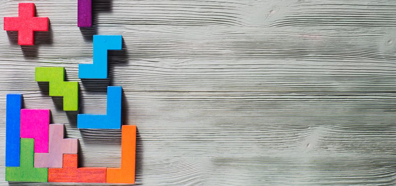 Bunte Tetris-Formen aus Holz auf hölzernem Hintergrund